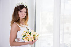 Young beautiful bride in white dress with flowers standing near. Young beautiful bride in white dress with rose flowers standing near the window Royalty Free Stock Photo