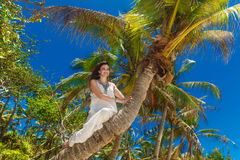 Young beautiful bride in white dress on the palm tree on a tropi Stock Photography