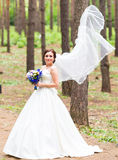 Young beautiful bride in white flying veil Royalty Free Stock Image