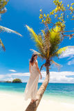 Young beautiful bride in white wedding dress on the palm tree on Royalty Free Stock Images