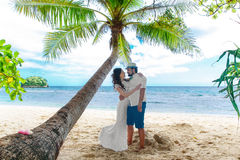 Young beautiful bride in white wedding dress on the palm tree an Stock Photography