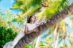 Young beautiful bride in white wedding dress on the palm tree on Royalty Free Stock Photography