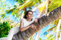 Young beautiful bride in white wedding dress on the palm tree on Stock Photography