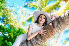 Young beautiful bride in white wedding dress on the palm tree on Royalty Free Stock Photos