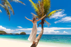 Young beautiful bride in white wedding dress on the palm tree on Stock Image