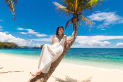 Young beautiful bride in white wedding dress on the palm tree on Royalty Free Stock Photo