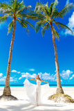 Young beautiful bride in white wedding dress under the palm tree Royalty Free Stock Photography
