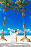 Young beautiful bride in white wedding dress under the palm tree Stock Photography