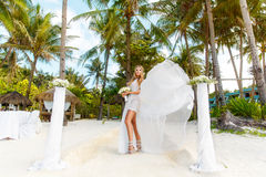 Young beautiful bride in white wedding dress under the palm tree Royalty Free Stock Images