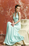 Young beautiful brown-haired woman in blue light silk dress Stock Images