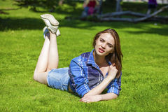 Young beautiful brown-haired woman lying on a lawn Stock Images