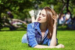 Young beautiful brown-haired woman lying on a lawn Royalty Free Stock Photography