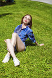 Young beautiful brown-haired woman lying on a lawn Stock Image