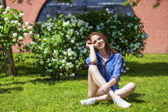 Young beautiful brown-haired woman sitting on the lawn Royalty Free Stock Photography