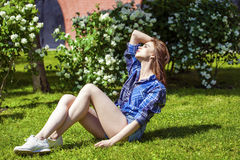 Young beautiful brown-haired woman sitting on the lawn Royalty Free Stock Images