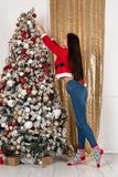 Young beautiful brunet girl in santa sweater decoretes the Christmas tree royalty free stock photos