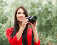 Young beautiful brunette being happy with new slr photo camera Royalty Free Stock Images