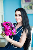 Young beautiful brunette in blue dress with a bouquet Stock Photography