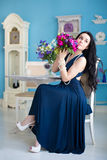 Young beautiful brunette in blue dress with a bouquet sitting on Stock Photo