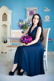 Young beautiful brunette in blue dress with a bouquet sitting on Stock Image