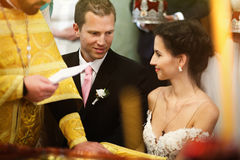 Young beautiful brunette bride and handsome groom with priest ta Stock Photography