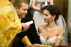 Young beautiful brunette bride and handsome groom with priest ta Royalty Free Stock Photo