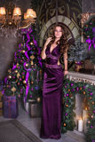 Young beautiful brunette costs in a violet long dress near a Christmas fir-tree. Nearby the burning candles and gifts Royalty Free Stock Photo