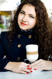 Young beautiful brunette with a delicious latte in a cafe Stock Images