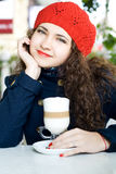 Young beautiful brunette with a delicious latte in a cafe Royalty Free Stock Images