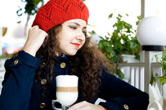 Young beautiful brunette with a delicious latte in a cafe Royalty Free Stock Photo