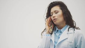 Young beautiful brunette doctor on a gray background. Wearing uniform medical uniforms. On a gray background suffering. From headache. Desperate and stressed stock footage