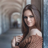 Young beautiful brunette in fashionable clothes near the wall. Portrait of a closeup girl royalty free stock photo