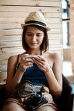 Young beautiful brunette female photographer looking at phone, smiling. Royalty Free Stock Images