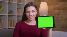 Young and beautiful brunette female shows horizontal green screen of tablet into camera recommending the app at home. Young and beautiful brunette female shows stock video footage