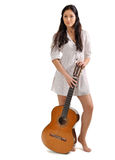Young beautiful brunette girl with acoustic guitar. Young beautiful brunette girl in white chemise with acoustic guitar royalty free stock photos