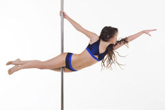 Young beautiful brunette girl doing pole dancing exercise Royalty Free Stock Photography