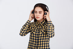Young beautiful brunette girl dressed in plaid shirt listening music in headphones looking away over white background Stock Photo
