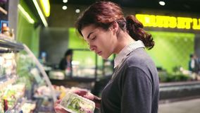 Young beautiful brunette girl in her 20`s trying to choose prepacked salad leaves in a grocery store.