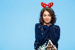 Young beautiful brunette girl in knited sweater and christmas reindeer antlers smiling  over blue background. Royalty Free Stock Photography