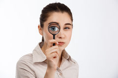 Young beautiful brunette girl looking with mistrust at camera through magnifier over white background. Royalty Free Stock Images