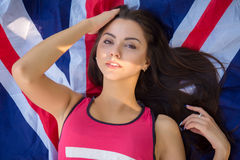 Young beautiful brunette girl posing with a British flag in autumn park. Young beautiful brunette girl posing with a British flag in sunny autumn park Stock Images