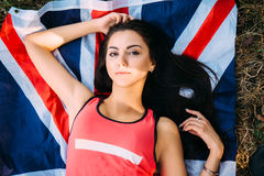 Young beautiful brunette girl posing with a British flag in autumn park. Young beautiful brunette girl posing with a British flag in sunny autumn park Royalty Free Stock Photos