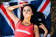 Young beautiful brunette girl posing with a British flag in autumn park. Young beautiful brunette girl posing with a British flag in sunny autumn park Royalty Free Stock Photography