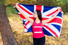 Young beautiful brunette girl posing with a British flag in autumn park Royalty Free Stock Image