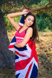 Young beautiful brunette girl posing with a British flag in autumn park Stock Photos