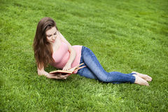 Young beautiful brunette girl reading a book outdoor Stock Images