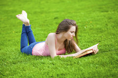 Young beautiful brunette girl reading a book outdoor Royalty Free Stock Image