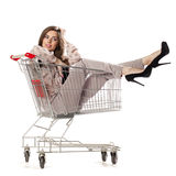 Young beautiful brunette girl sits in an empty shopping cart Stock Photography