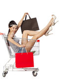 Young beautiful brunette girl sits in an empty shopping cart wit Royalty Free Stock Photo
