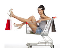 Young beautiful brunette girl sits in an empty shopping cart wit Stock Photo